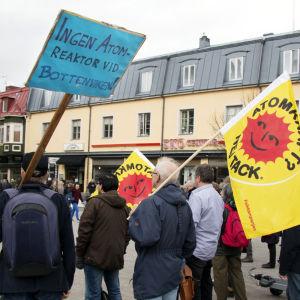 Demonstration mot kärnkraften i Umeå centrum, människor med plakat och flagga