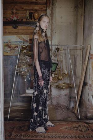 En modell poserar i en gammal stuga iklädd en svart genomskinlig topp och en huvudduk med ljusa blommor.