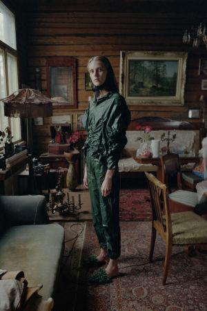En modell poserar i en stuga med gammaldags inredning. Modellen bär en svartgrön klänning och en huvudduk.
