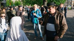 En man som filmar en kvinna i muslimsk klädnad.