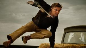 Rick Dalton hoppar av ett pick up-flak med ett gevär i högsta hugg.