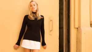 Margot Robbie poserar i svart polo och vit minikjol.