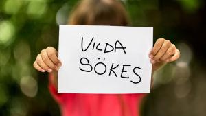 """Flicka håller upp papper med texten """"Vilda sökes"""""""