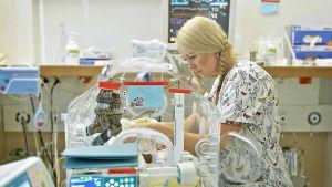 Kätilö-Martiina huolehtii kaksi päivää sitten keskosena syntyneestä Eetusta.