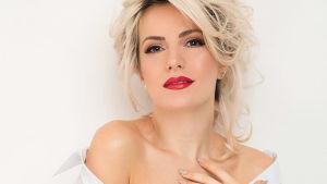Vaaleahiuksinen nainen siistissä meikissä ja punaisissa huulissa katsoo suoraan kameraan, päällään hänellä on valkoinen kauluspaita, joka valuu alas hartioilta. Käsivarsissa värikkäitä tatuointeja.