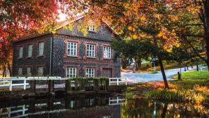 Bild på hus i Fiskars, solen skiner bakom det och löven är orangefärgade.