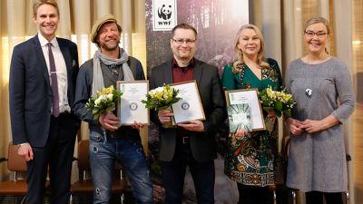 Antti Reini (andra från vänster) poserar med diplom och blombukett tillsammans med fyra andra personer. I bakgrunden syns en WWF-plansh.