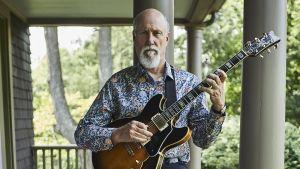 Jazzmuusikko John Scofield kitara kädessä talon terassilla.