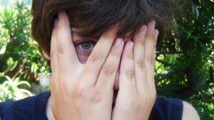 ung kille(?) som gömmer ansiktet  i händerna, ena ögat syns.