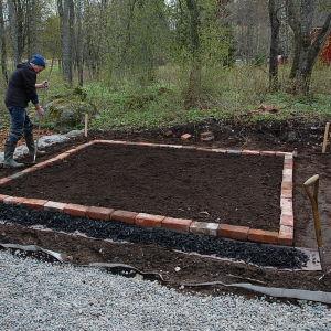 Owe Salmela anlägger potagere-trädgården på Strömsö, breder ut myllan.