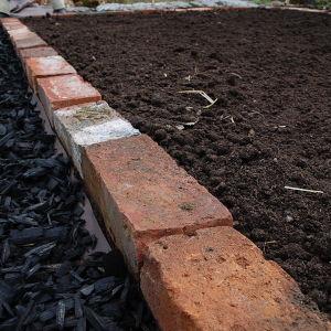 Svart flis, rödtegel och mylla vid potagere-trädgården
