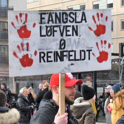 """En demonstrant håller en skylt där det står """"Fängsla Löfven och Reinfeldt""""."""