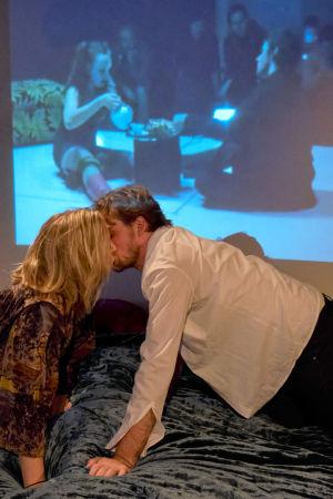 Milla Kangas (Sarah) ja Lauri Tilkanen (Richard) nojautuvat sängyn yli suutelemaan toisiaan. Seinään on heijastettu kuva samoista näyttelijöistä 10 vuoden takaisessa versiossa samasta näytelmästä.