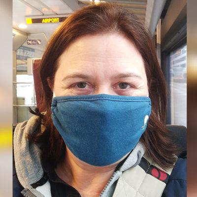 Kapellimestari Anna-Maria Helsing lentokenttäjunassa maski kasvoilla.