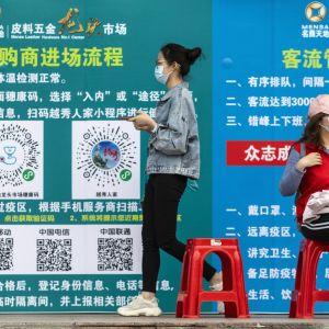 Nainen kävelee ja toinen istuu, taustalla seinän peittävä juliste.