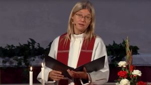 Liturgen Hanna Eisentraut-Söderström läser en text vid altaret och ser ut mot församlingen i Borgå kyrka. Liturgiska färgen på stolan är röd.
