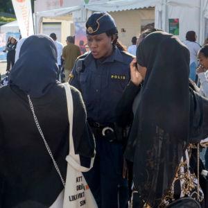 En polis står och pratar om sitt yrke med ett par kvinnor i slöjor.