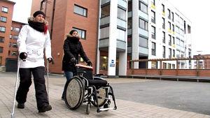 Wilma Dufva kävelee kyynärsauvojen kanssa ja avustaja Anne Härkönen pukkaa pyörätuolia.