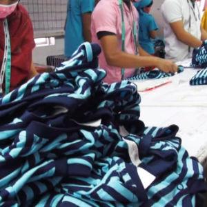Työläiset tarkastavat paitoja bangladeshilaisessa vaatetehtaassa.