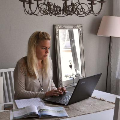 Ela Strandberg sitter vid sitt vita matbord hemma vid sin dator.