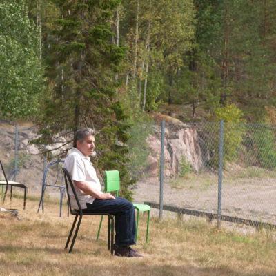 Dokumentin yksi henkilöistä istuu ulkona aidan sisäpuolella