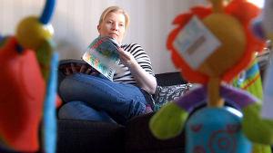 Susanna Mäki-Petäjä istuu sohvalla ja lukee lehteä.