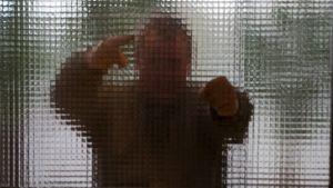 Våldsam man bakom en glasvägg.