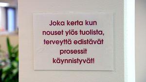 Taulu toimiston seinällä: Joka kerta kun nouset ylös tuolista, terveyttä edistävät prosessit käynnistyvät.