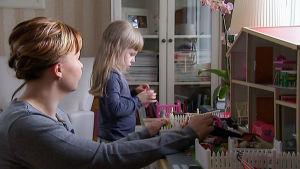 Heli ja Miisa Liuha leikkivät nukkekodilla.