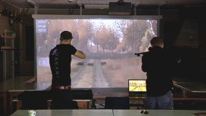 Två personer övar på en jaktsimulator