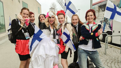Krista iklädd brudklänning tillsammans med sina dansare på väg mot finalen i Eurovisionen. De poserar med Finlands-flaggor och ler rakt in i kameran.