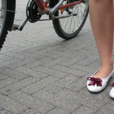 Tyttö taluttaa pyörää jalkakäytävällä.