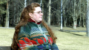 Anu Wickholm istuu puistonpenkillä.