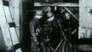 Kaivosmiehet hississä matkalla alas kuiluun.