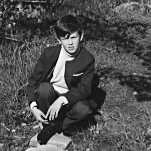 Nuori oppikoulunsa aloittava Rainer mahlamäki kotitalonsa pihalla kyykistyneenä puettuna parhaimpiinsa.