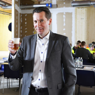 En medelålders man som är stadsdirektör Jan D. Oker-Blom ler mot kameran och håller upp en plastmugg med öl.