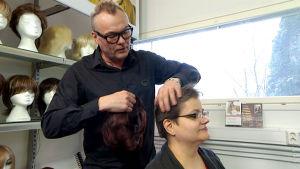 Kari Hartman sovittaa Sari Laaksolle peruukkia.