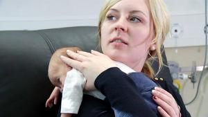 Anuliina Aalto pitelee vastasyntynyttä lastaan sylissä.