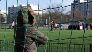 Nainen seisoo jalkapallomaalin takana.