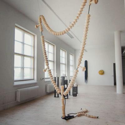 Sisäkuva taidekeskus Antareksen näyttelytilasta, korkea valkoinen tila, jossa katosta roikkuva puuhelmistä koottu veistos