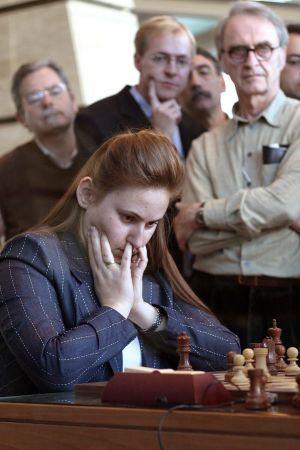 En kvinna spelar schack. Flera män står runt omkring henne och tittar på.