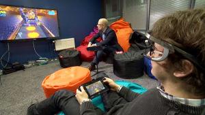 Jukka Vahlo pelaa tietokonepeliä ja Aki Koponen seuraa vierestä.