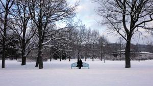 Nainen istuu puistonpenkillä ja pitää maskia kasvoillaan.