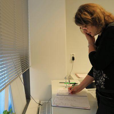 Parturi-kampaaja Minna Hyytiäinen puhuu puhelimessa ikkunan ääressä.