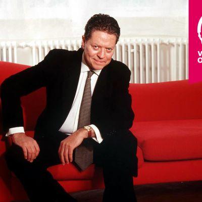 Robert Palmer sitter på en soffa.