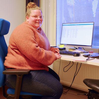 En kvinna i orange tröja sitter framför ett skrivbord med två datorskärmar. Hon ler och tittar in i kameran. Bakom henne syns en bäddad säng.