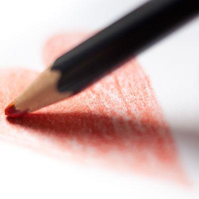 Punaista sydäntä piirretään paperille puuvärillä.