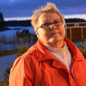 En medelålders kvinna i glasögon och röd jacka står utomhus. Lampor på gårdsplanen lyser upp hennes ansikte. Bakom henne synns hav och holmar.