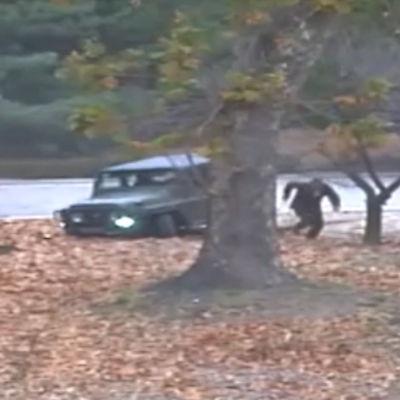 Nordkoreansk soldat springer från en jeep över gränsen mot Sydkorea.