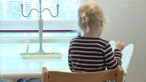 Barn sitter ensamt inomhus